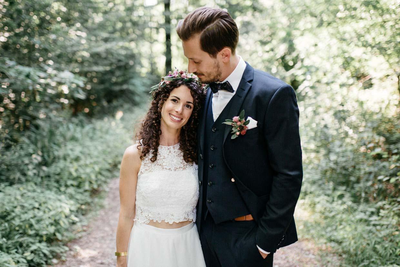 Bräutigam umarmt die Braut und Braut lächelt in die Kamera