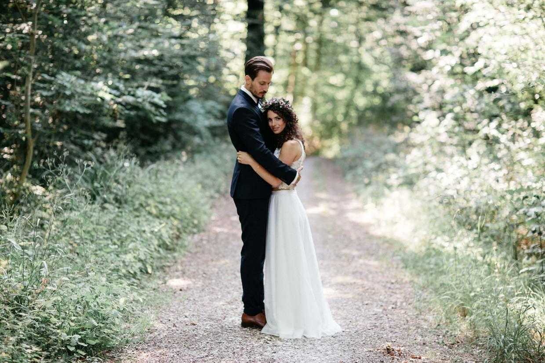 Brautpaar steht sich gegenüber und umarmt sich während die Braut in die Kamera schaut