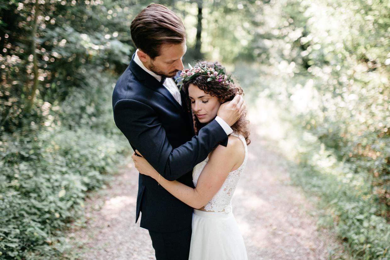 Brautpaar steht sich gegenüber und Bräutigam streicht der Braut zärtlich durch die Haare