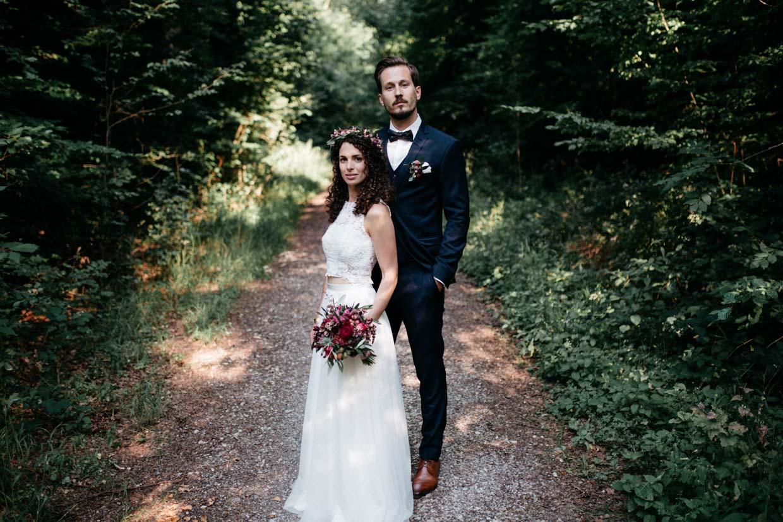 Brautpaar seht hintereinander und schaut cool in die Kamera