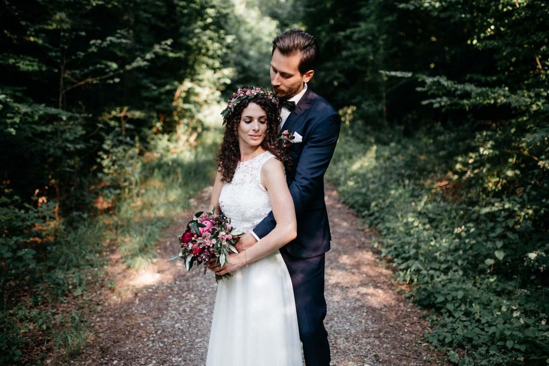 Bräutigam steht hinter der Braut und umarmt sie