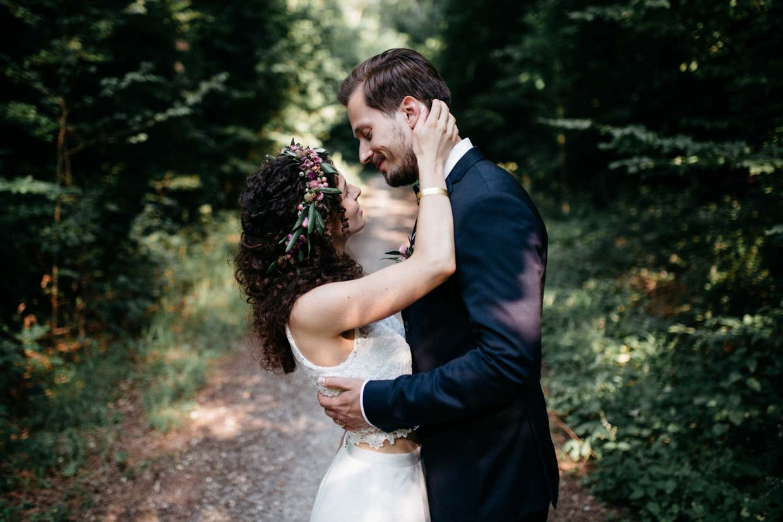 Braut hält den Hinterkopf des Bräutigams und lächelt ihn an