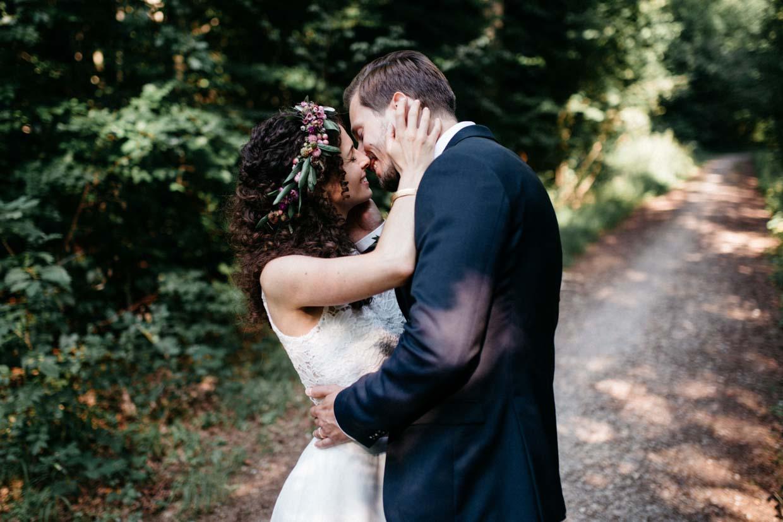 Braut hält den Hinterkopf des Bräutigams und küsst ihn