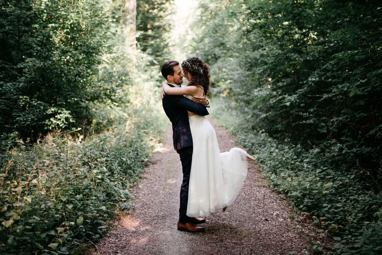 Brautpaar umarmt sich und Bräutigam hebt die Braut hoch