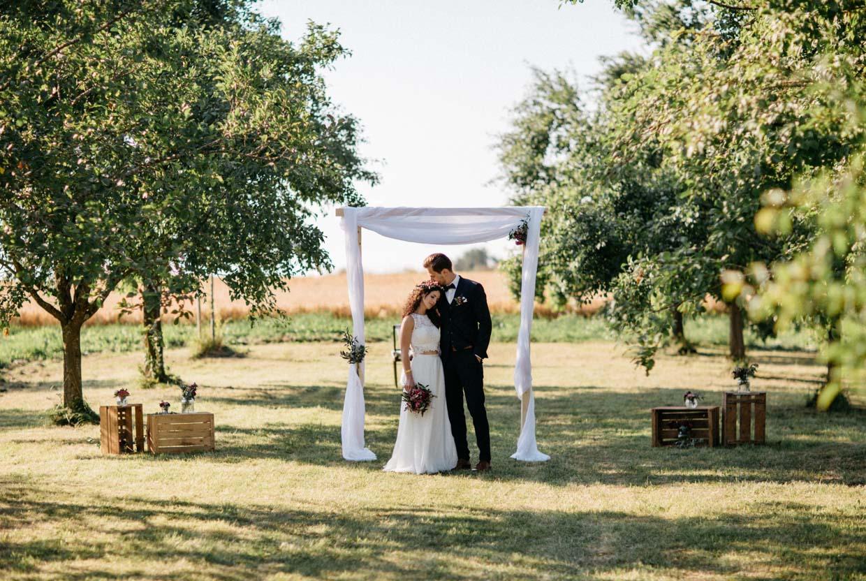 Brautpaar steht vor einem Holzportal auf einer Obstwiese und umarmt sich