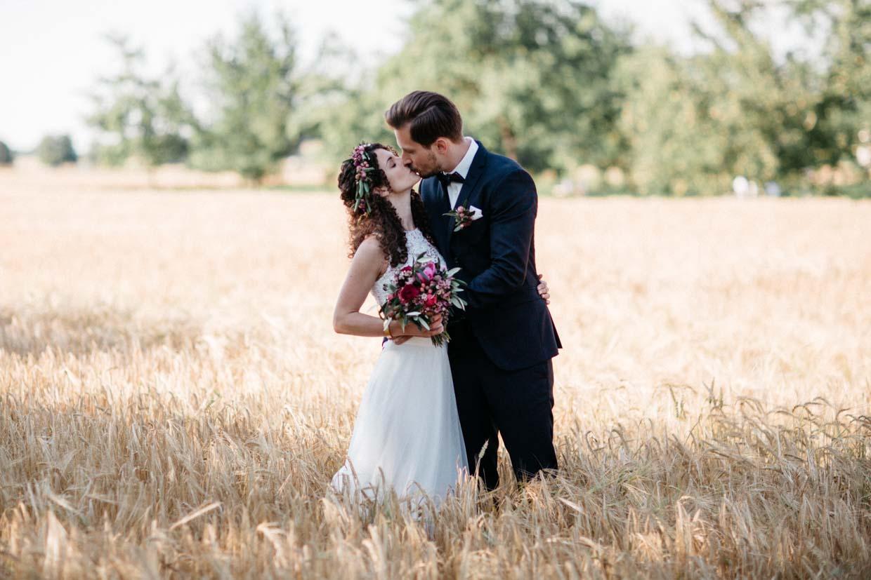 Brautpaar küsst sich im Weizenfeld
