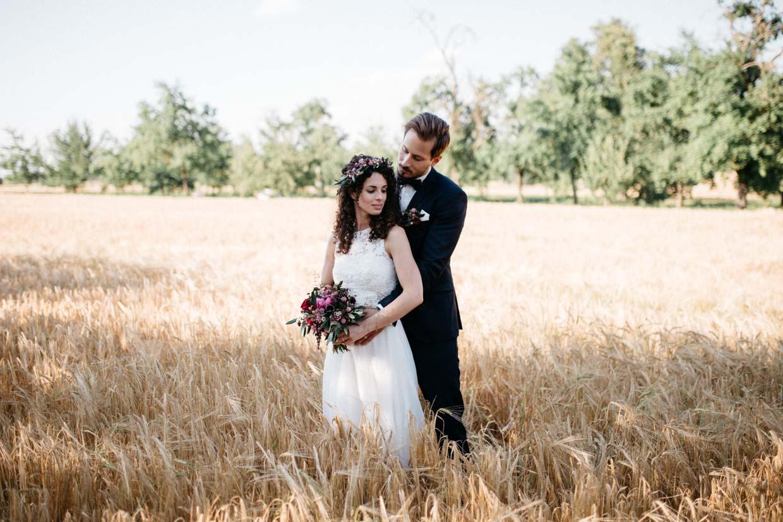 Brautpaar steht hintereinander im Weizenfeld