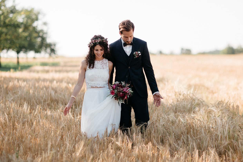 Brautpaar geht gemeinsam durch ein Weizenfeld