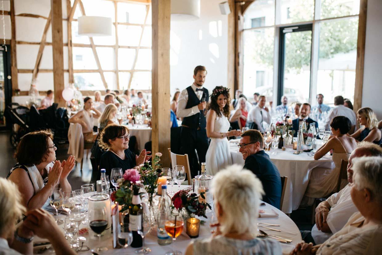 Hochzeitsgäste freuen sich während der Rede des Brautpaares