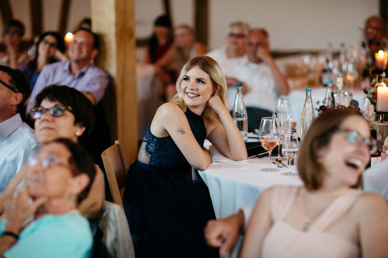 Hochzeitsgäste schauen sich eine Beamer-Show an und freuen sich