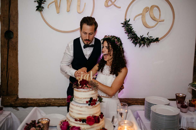 Brautpaar schneidet die Hochzeitstorte an und Braut lacht authentisch und emotional