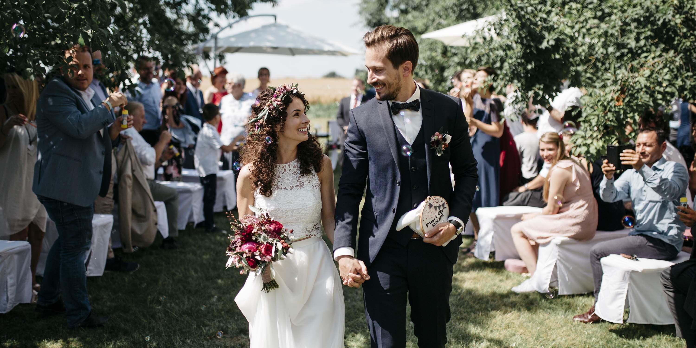Brautpaar freut sich beim Auszug nach der Trauung