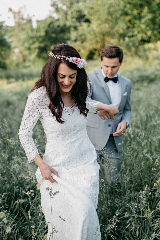Brautpaar läuft Hand in Hand aus einem Wiesenfeld heraus