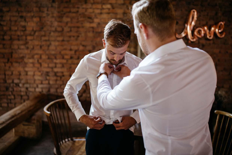 Trauzeuge hilft dem Bräutigam beim Hemdanziehen