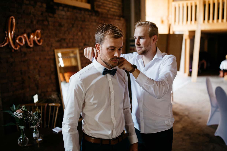 Trauzeuge legt dem Bräutigam die Fliege an