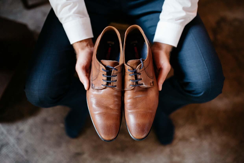 Bräutigam hält Schuhe in den Händen