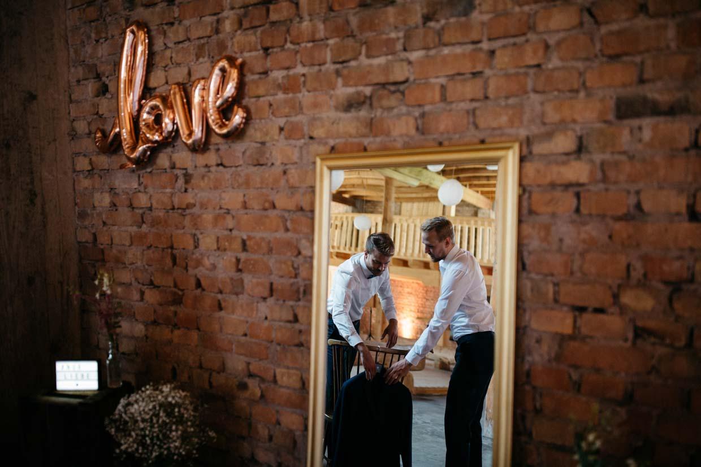 Aufnahme eines Spiegels in dem der Bräutigam seinen Anzug nimmt