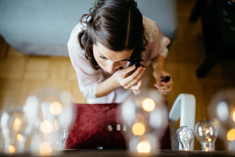 Braut sitzt vor einem Spiegel und schminkt sich