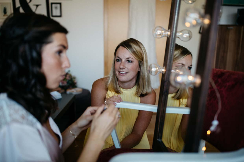 Trauzeugin schaut der Braut beim Schminken zu