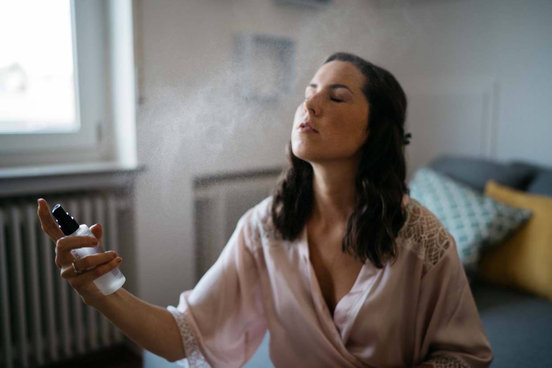 Braut sprüht sich Parfüm ins Gesicht