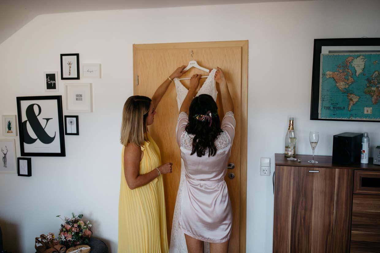 Braut und Trauzeugin nehmen das Brautkleid