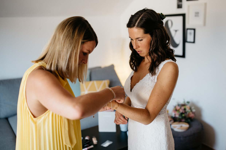 Trauzeugin legt der Braut eine Armkette an