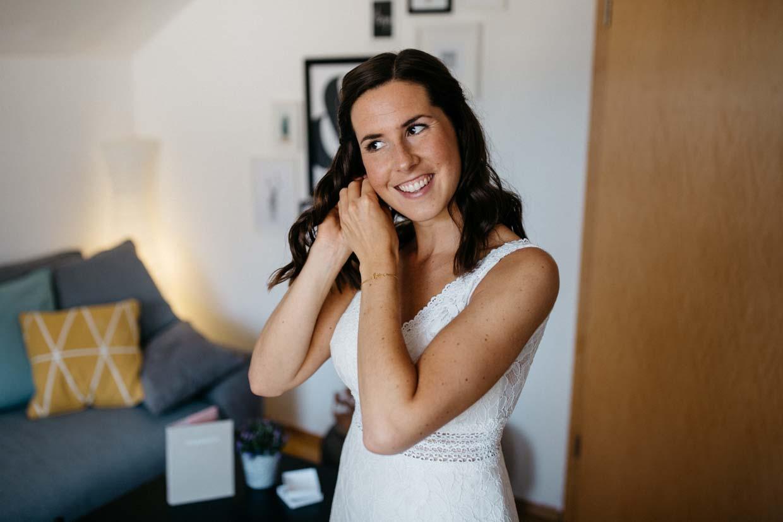 Braut zieht sich Ohrringe an und lächelt dabei