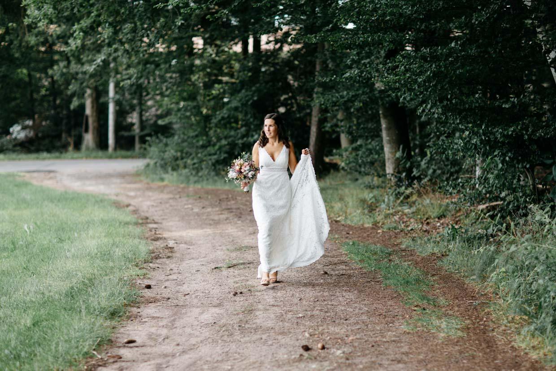 Braut geht einen Feldweg entlang