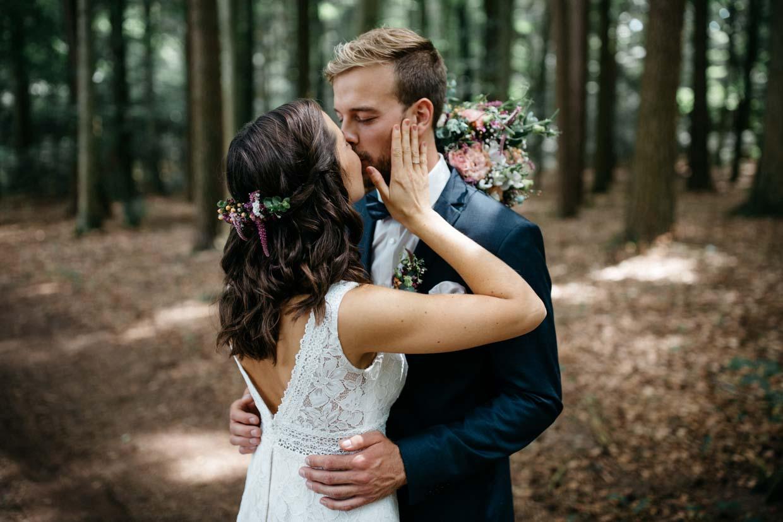 Braut hält sanft das Gesicht des Bräutigams und küsst ihn dabei
