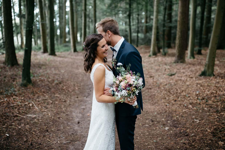Brautpaar steht im Wald und lacht gemeinsam