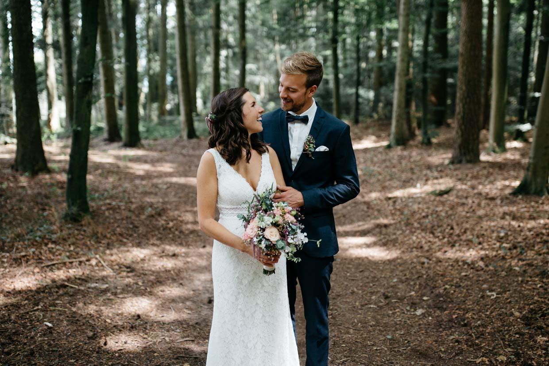 Brautpaar steht hintereinander und lacht