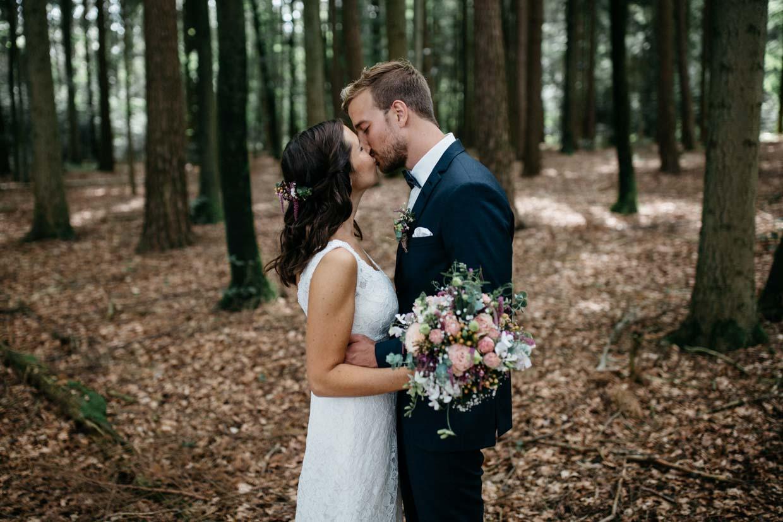 Brautpaar steht sich gegenüber und küsst sich