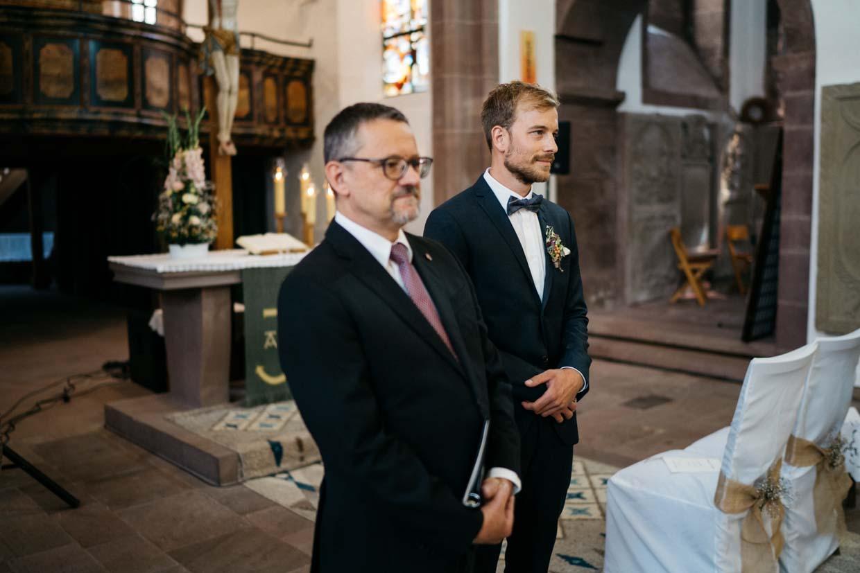 Bräutigam und Pfarrer stehen am Altar und warten auf die Braut