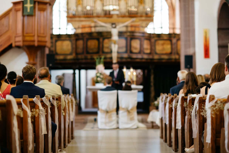 Kirchengang mit Brautpaar und Hochzeitsgästen von hinten unscharf fotografiert