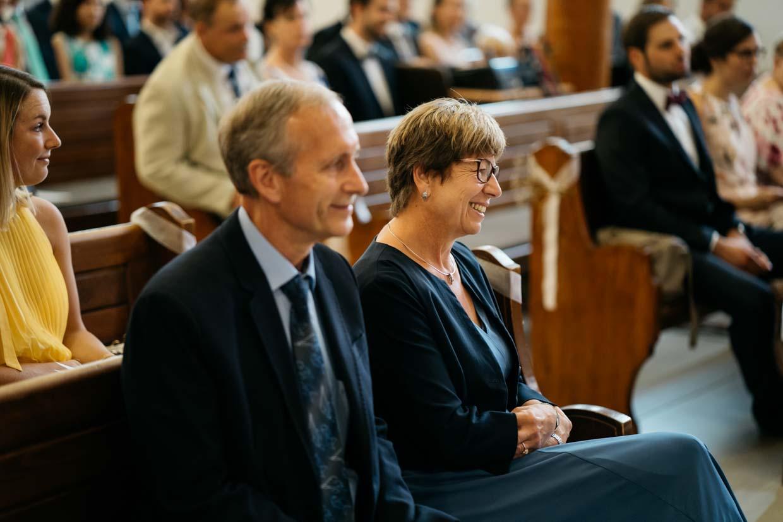 Hochzeitsgäste sitzen in der Kirche und lachen