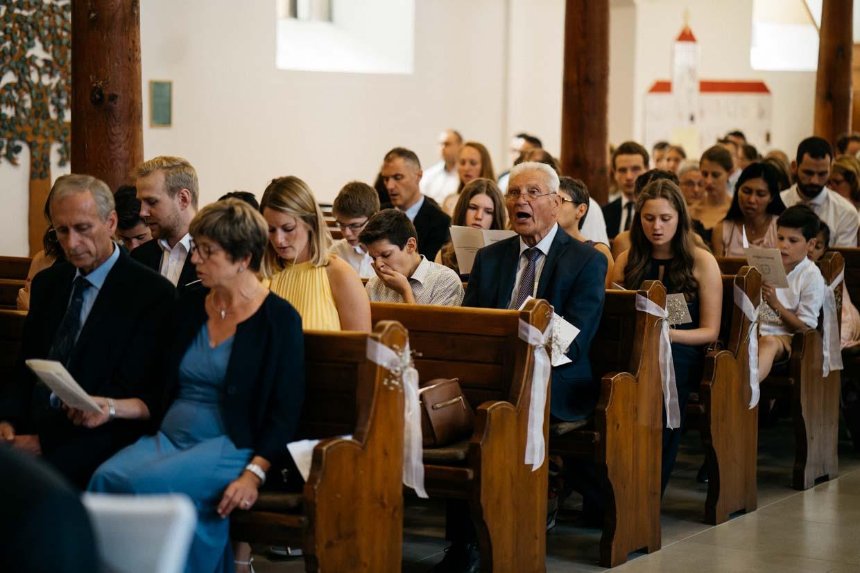 Hochzeitsgäste sitzen in der Kirche und singen