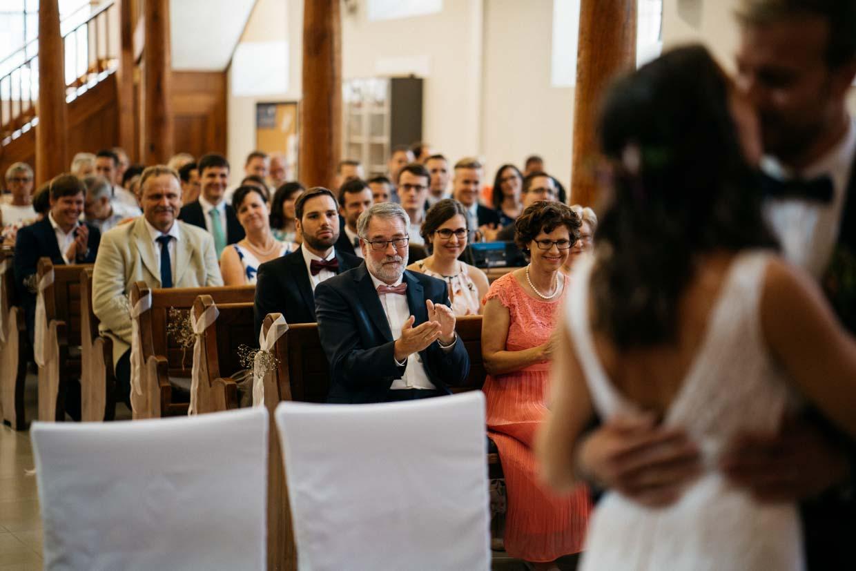 Hochzeitsgäste applaudieren beim ersten Kuss während der kirchlichen Trauung