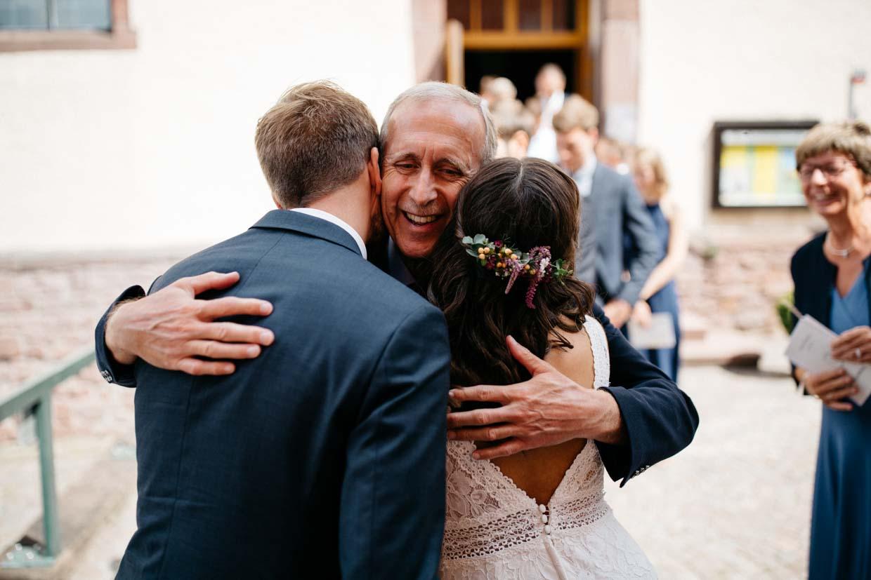 Gast umarmt Braut und Bräutigam gleichzeitig