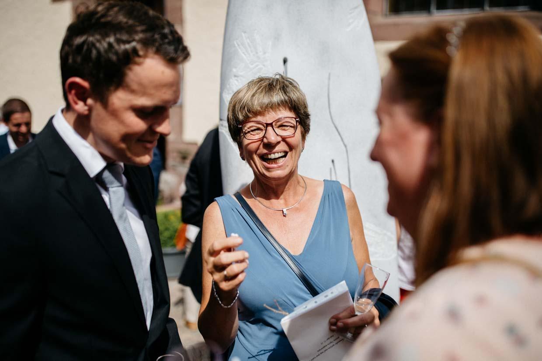 Hochzeitsgäste lachen beim Sektempfang