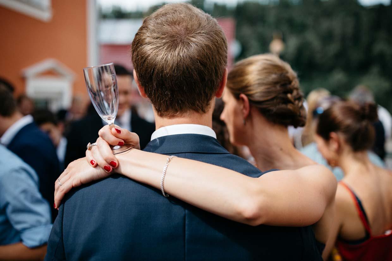 Frau umarmt ihren Mann und hält dabei ein leeres Sektglas in der Hand
