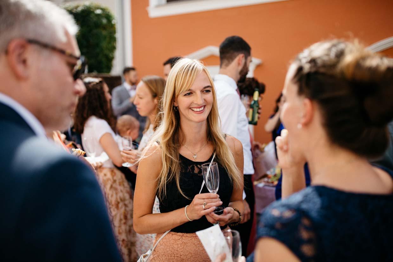 Hochzeitsgäste stehen beim Sektempfang zusammen