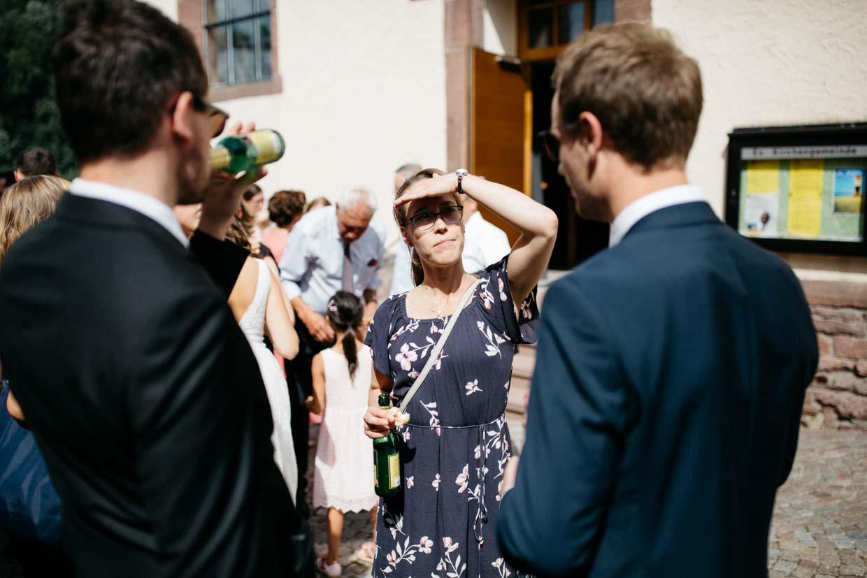 Frau unterhält sich mit zwei Männern und hält sich die Hand vor die Stirn