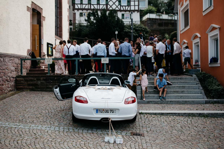 Porsche steht vor der Kirche beim Sektempfang mit angehängten Dosen