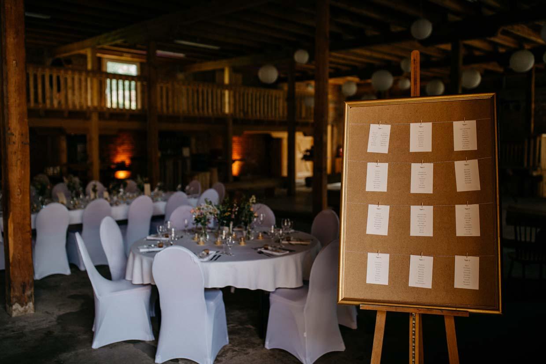 Raumaufnahme einer Hochzeitslocation mit Sitzplan im Vordergrund
