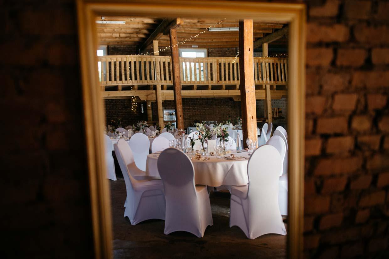 Raumaufnahme einer Hochzeitslocation durch den Spiegel fotografiert