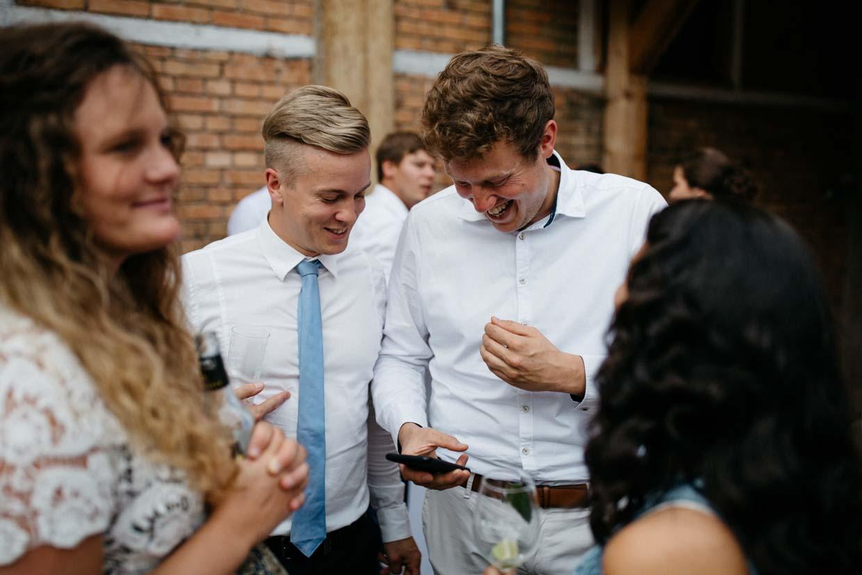 Gäste schauen ins Handy und lachen