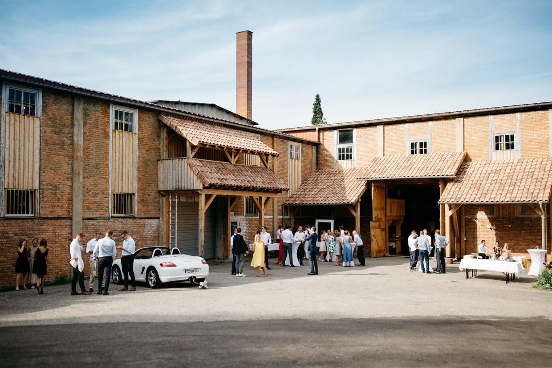 Hochzeitsgäste stehen vor einem Fabrikgebäude und unterhalten sich