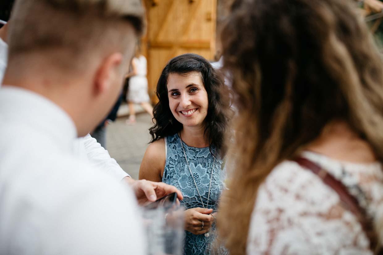 Hochzeitsgäste stehen beisamen und eine Dame lächelt freundlich in die Kamera