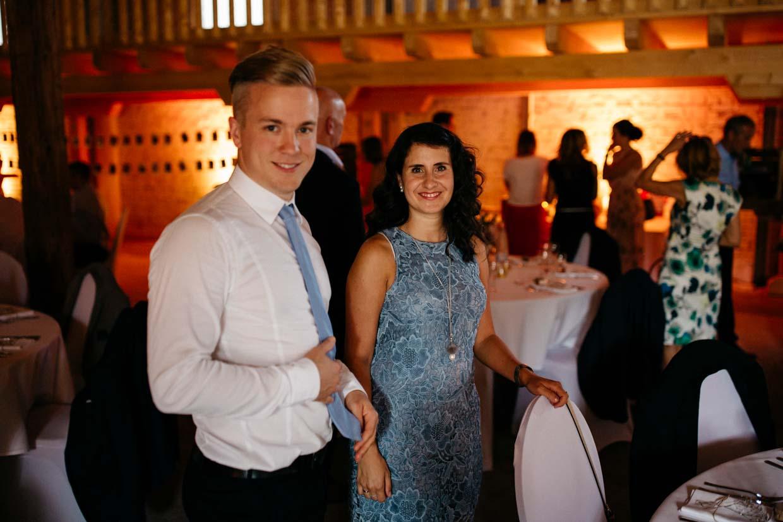 Hochzeitsgäste stehen am Tisch und lächeln in die Kamera
