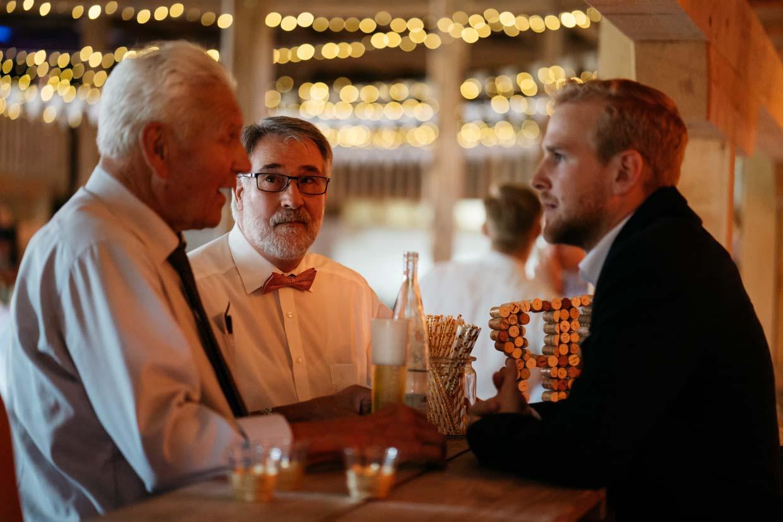 Hochzeitsgäste stehen an der Bar und unterhalten sich